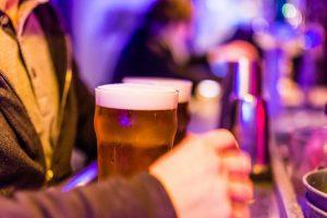 man aan de bar met glas bier